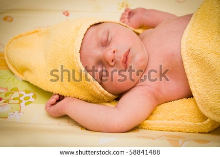 Newborn baby boy sleeping after bath covered by yellow towel - stock photo
