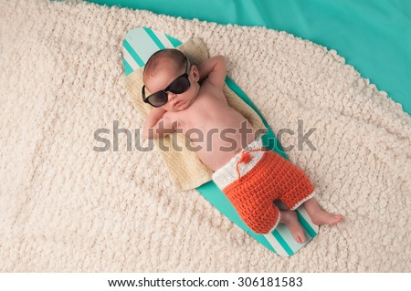 Newborn baby boy sleeping on a tiny surfboard. He is wearing black sunglasses and crocheted boardshorts. - stock photo