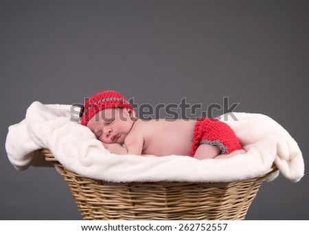 Newborn baby boy sleeping on a white blanket in a wicker basket. Infant is wearing a red knit cap and diaper cover. Background is grey seamless paper.  - stock photo
