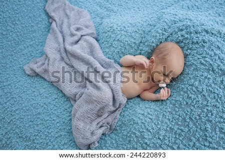 newborn baby boy sleeping on blue - stock photo
