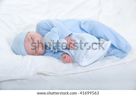 Newborn baby boy wearing blue pajamas with hat holding a teddy bear - stock photo
