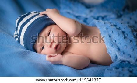 Newborn baby boy with blue beanie lies awake under blue blankets - stock photo