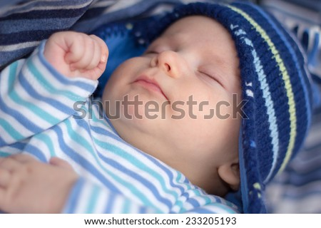 Newborn baby boy with striped hat and pajama sleeping on a blue blanket. Shallow Focus - stock photo