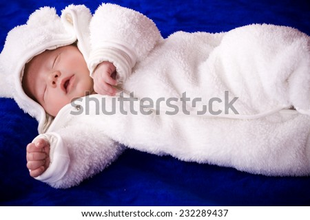 Newborn baby child wearing a white sleeper.  - stock photo