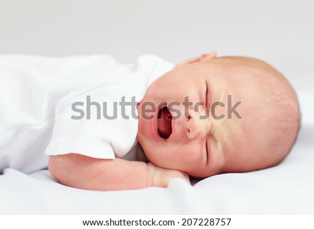 newborn baby crying because of cramps - stock photo