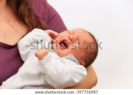 Newborn baby crying in his mother's arms - stock photo
