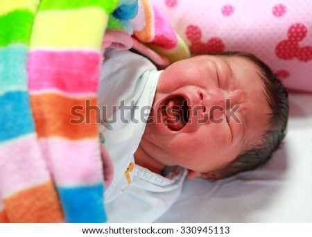 Newborn baby (2 day old) screaming in baby cot bed - stock photo
