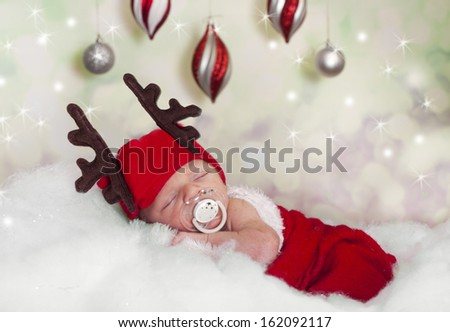 newborn baby dressed up as a reindeer  - stock photo