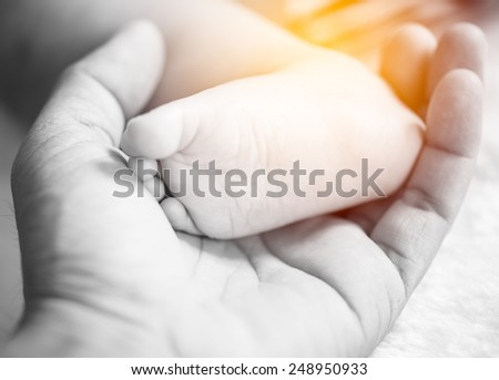 newborn baby feet on male hand in vintage filter style - stock photo