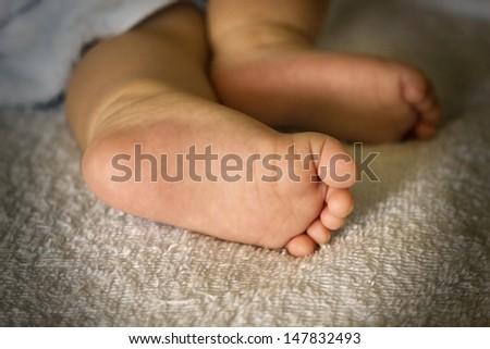 Newborn baby feet shown in close up - stock photo
