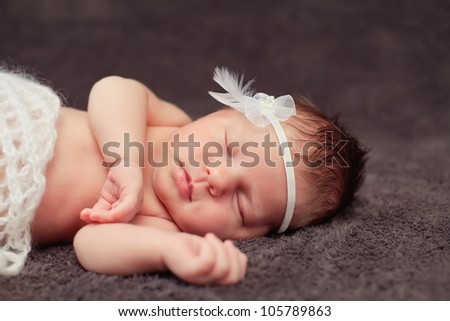 Newborn baby girl asleep on a blanket. - stock photo