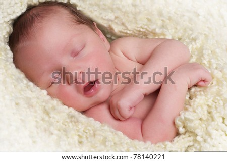 Newborn baby girl asleep on a knitted blanket. - stock photo