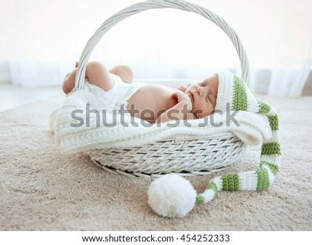 Newborn baby girl, 7 days old, sleeping on soft blanket in a basket - stock photo