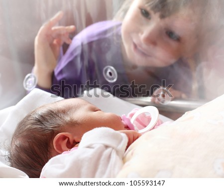 Newborn baby girl in a incubator. Her sister looking at. - stock photo