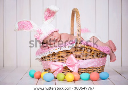 Newborn baby girl in a rabbit costume has sweet dreams on the wicker basket. Easter Holiday - stock photo