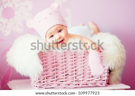 newborn baby girl in pink knitted bear hat lies at basket - stock photo