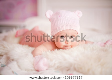 newborn baby girl in pink knitted bear hat lies at fur - stock photo