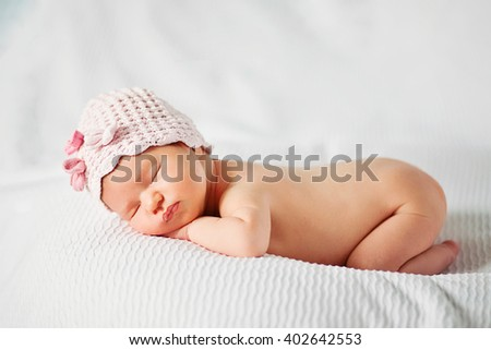 newborn baby girl in pink knitted hat with flowers - stock photo