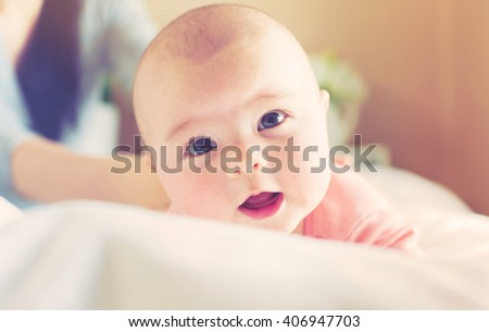 Newborn baby girl lying being cared for by her mother - stock photo