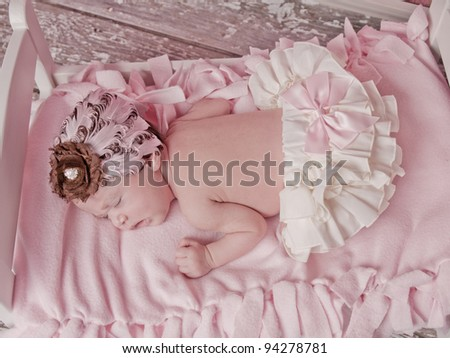 Newborn baby girl one week old asleep in her bed with with bloomers and a pink bow and a feathered headband. - stock photo