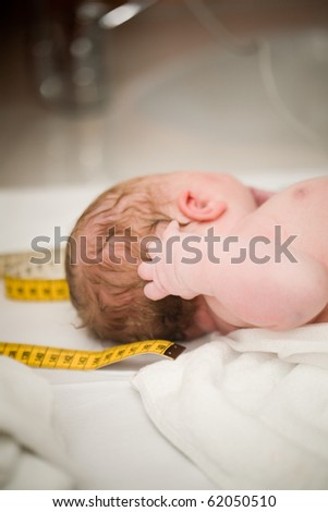Newborn baby girl right after delivery, shallow focus - stock photo