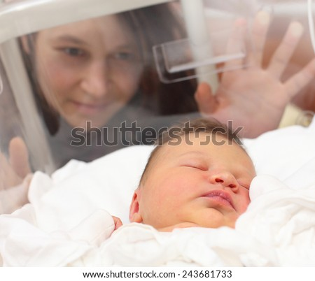 Newborn baby girl sleeping in a incubator. Her mother looking at. Close up with shallow DOF.  - stock photo