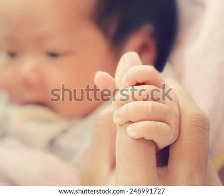 Newborn baby holding mother's hand - stock photo