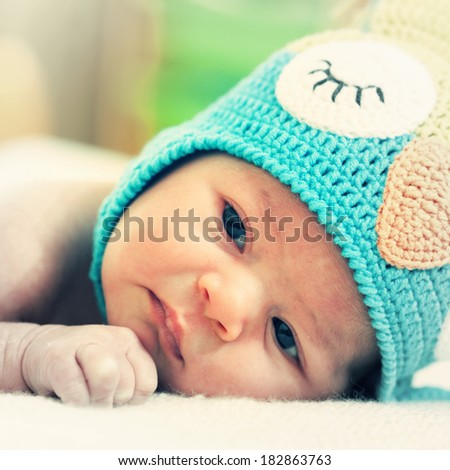newborn baby in a bright knitted hat - stock photo
