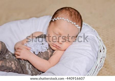 newborn baby in a dressy brown and white jumpsuit and a headband is sleeping in white basket - stock photo