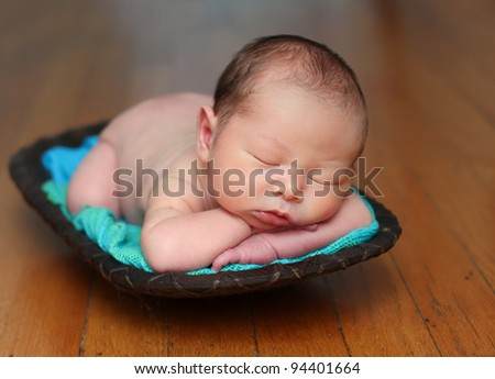 Newborn baby in a wood bowl, mix race: Caucasian and Asian - stock photo