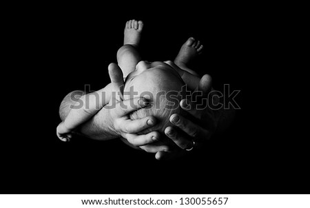 Newborn baby in fathers hands, black and white - stock photo