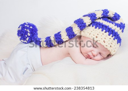 Newborn baby in gnome hat is sleeping on the white fluffy blanket - stock photo