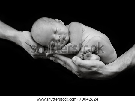 Newborn baby in hands, shallow depth of field, low key lighting - stock photo