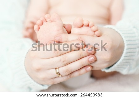Newborn baby in mother hugs, close-up - stock photo