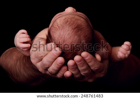 Newborn baby in the arms of his father, close-up, black background - stock photo