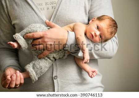 newborn baby in the hands of the father - stock photo