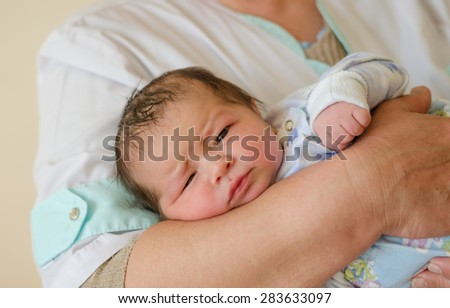 Newborn baby in the hands of the obstetrician. - stock photo