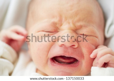Newborn baby is crying - selective focus - stock photo