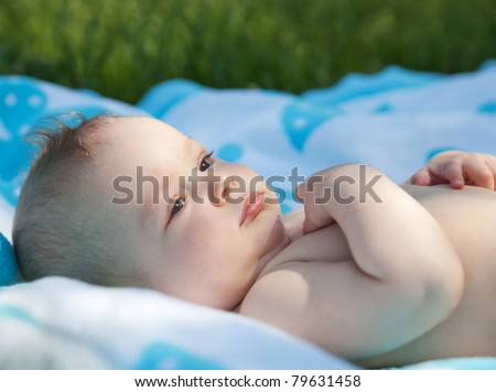 Newborn baby lay on towel in park - stock photo
