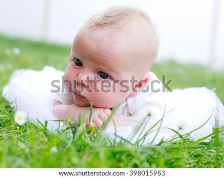 Newborn baby laying on the grass - stock photo