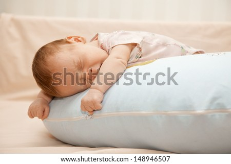 Newborn baby laying on the pillow on his tummy and yawning - stock photo