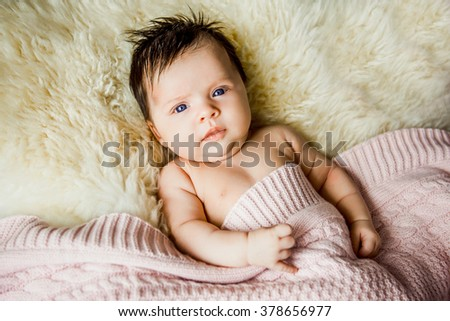 newborn baby lying with open eyes in crib. Shelter pink baby blanket - stock photo