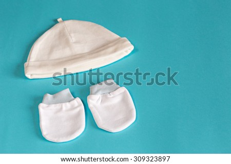 Newborn baby mittens and a cap on a blue pastel background.  - stock photo