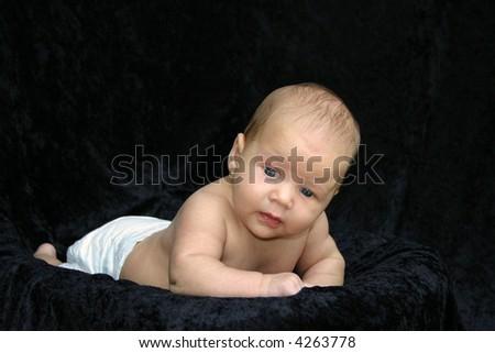 Newborn baby on black background - stock photo