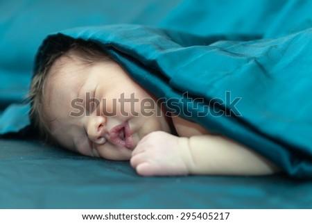 newborn baby on dark sheet - stock photo