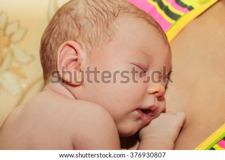 Newborn baby peacefully sleeping.Adorable beautiful newborn baby girl. Maternity and newborn concept. Adorable beautiful newborn baby cradled in its mothers hands looking up with a look of wonderment - stock photo