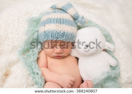 Newborn Baby sleeping, asleep with a stuffed toy, on a blanket, wearing a knit hat - stock photo