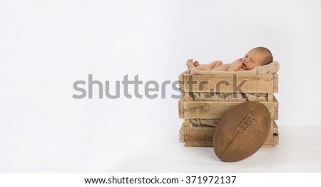 Newborn baby sleeping in a vintage wooden crate on a white backdrop with a rugby ball in front of the crate. - stock photo