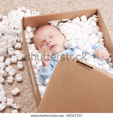 Newborn baby sleeping in open post box with filler represented on carpet. Small baby relaxing in box and dreaming about freedom. - stock photo