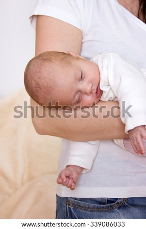 Newborn baby sleeping in the arms of his mother / newborn / baby - stock photo